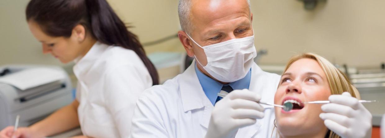 Tandarts met mondkapje behandeld een vrouw