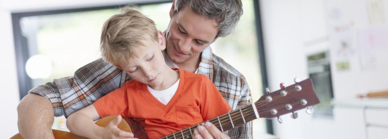 Man leert zoon gitaar spelen