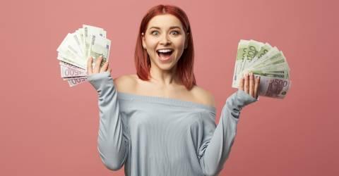 Een lachende jonge vrouw met bankbiljetten in haar hand